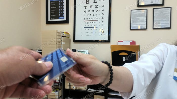 Guy paying with credit card at eye doctor...