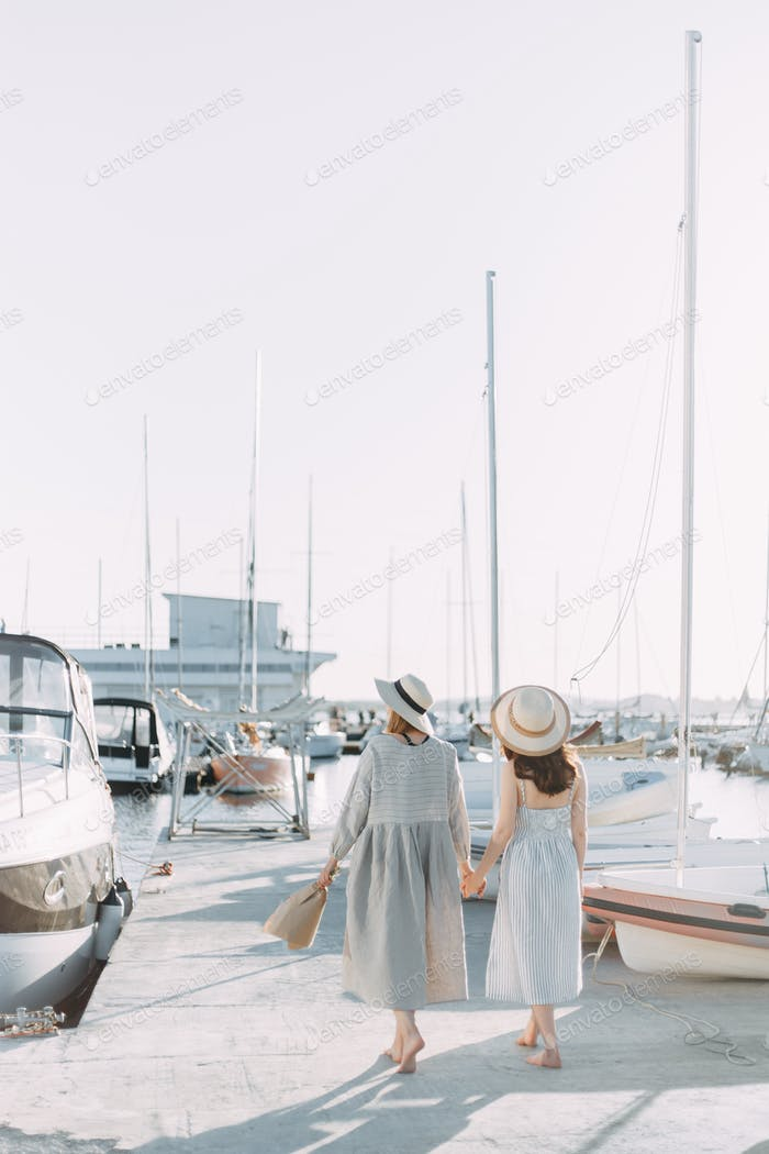 two happy girls in love in summer dresses and hats walk relax and sunbathe on the pier in the sea