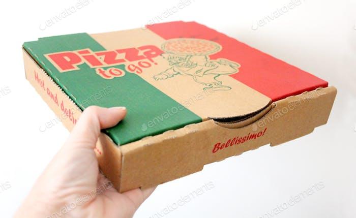 Holding a cardboard takeaway pizza box