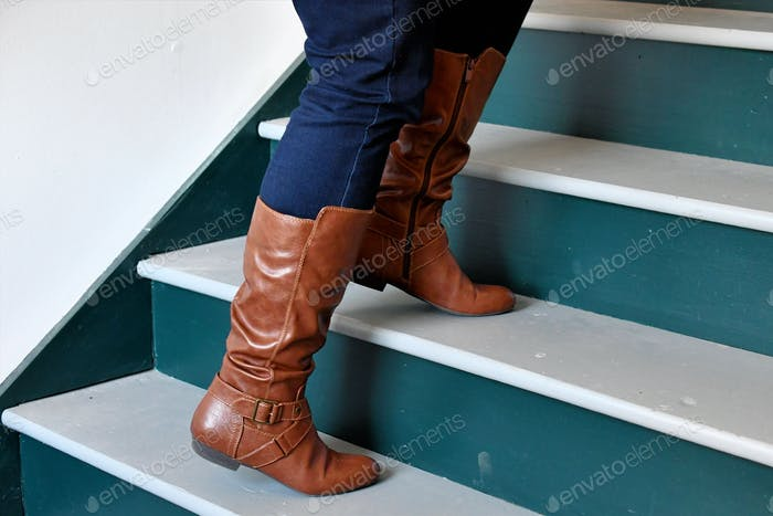 Walking up steps in stylish winter boots and skinny jeans. Gender equality