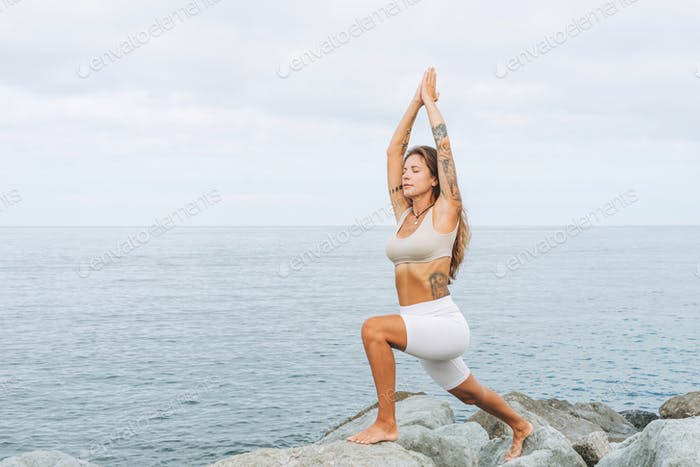 Young carefree beautiful woman with long hair in white clothes practice yoga on the sea beach