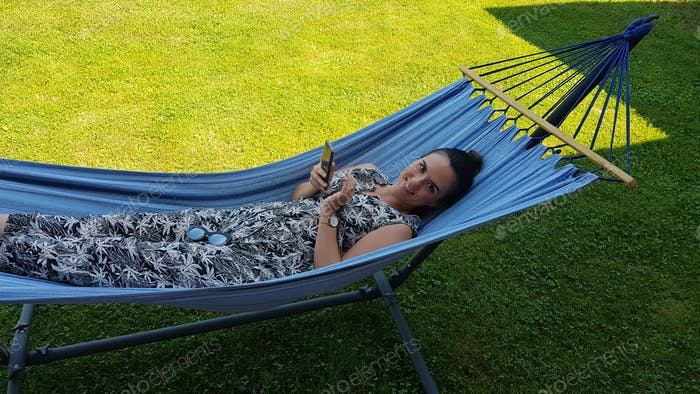 Young millenial woman relaxing on a blue hammock