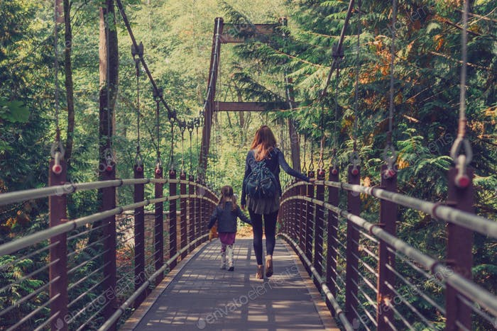 Mother and daughter crossing a bridge in the woods