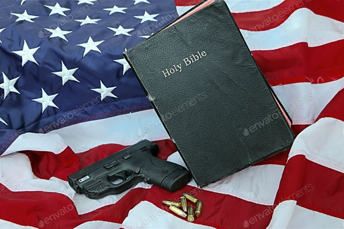 The Bible and a .9mm and bullets on an American flag background.