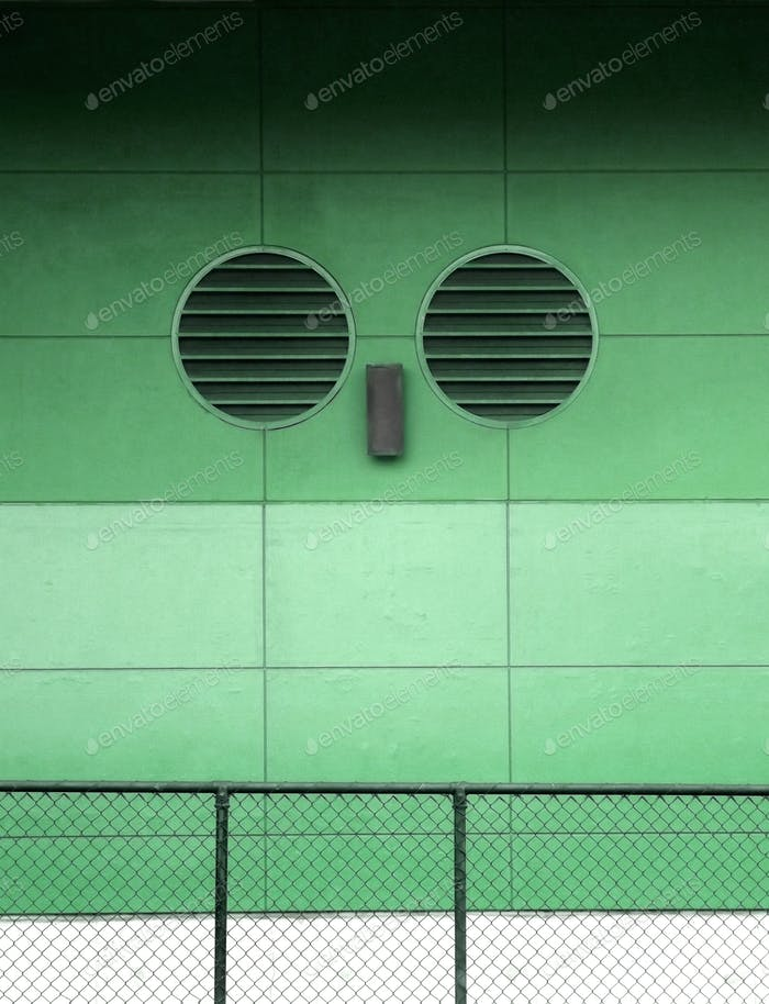 Minimalism - air vents on a concrete wall with fence in front
