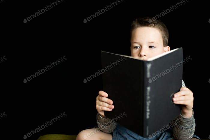 Boy reading a book on a kindle e-reader against a black backdrop