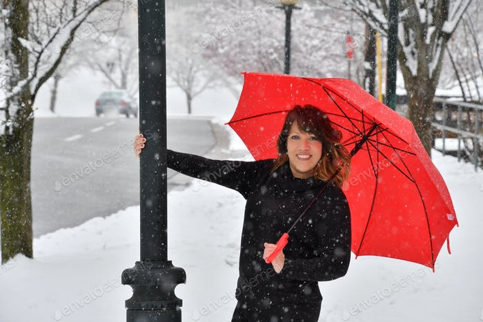 A Puerto Rican Latino woman laughing enjoying a snow day in the city with a red umbrella.