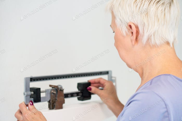 Senior adult woman checking her weight on the scales