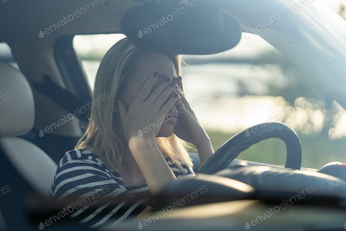 Stressed woman cry in car. Middle age lady driver hide face in hands afraid to drive after accident