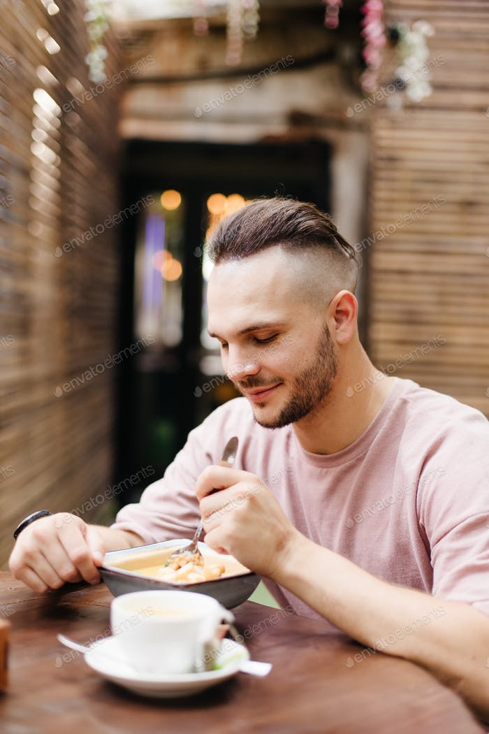 Man eating soup in cafe