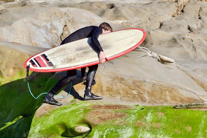A surfer climbs the mossy green cliffs carrying his surfboard after a great Winter surf session