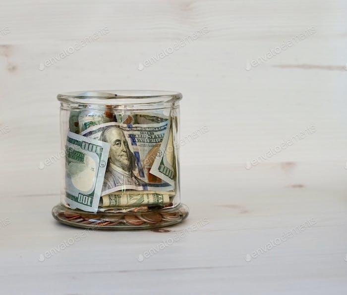 Ein Glas Bargeld und Münzen Ein Glas voller Bargeld und Münzen Moneymatters Bailout