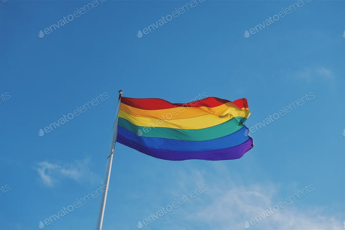 Rainbow flag gay rights marriage equality against blue sky