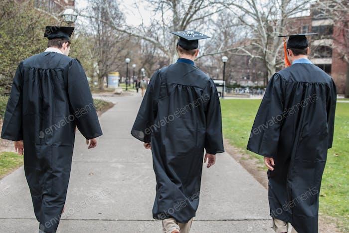 Three college graduates walking in graduation robes.