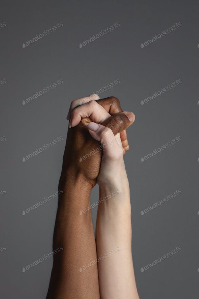 Pareja interracial tomada de la mano sobre fondo gris.