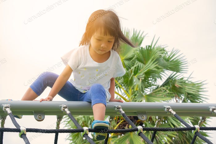 Challenge mission and achievement. A little girl is climbing up the rope wall at the playground.