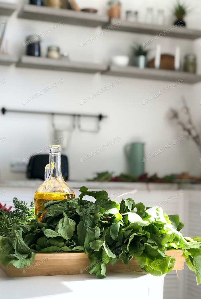 Fresh herbs lie on a wooden tray on a white table, front view.