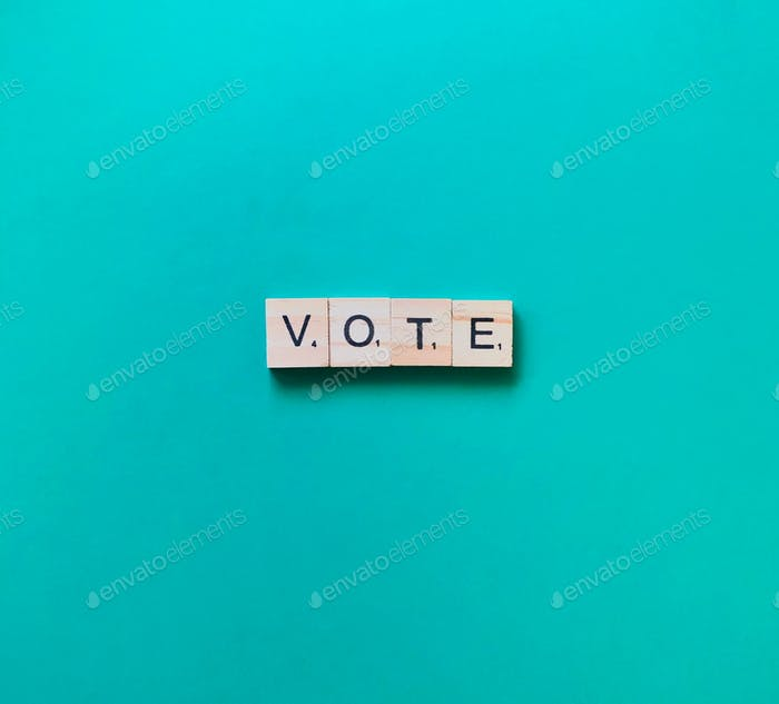 the word vote written in wooden scrabble tiles on a plain empty blue green bold bright background