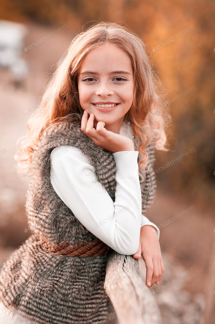 Smiling teen girl 12-14 year old wearing stylish fur vest and knitted sweater posing outdoors