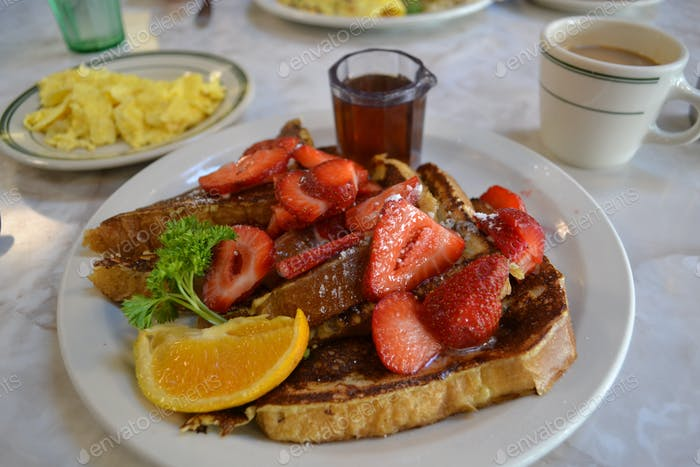 A generous portion of French toast served with sliced strawberries, maple syrup and scrambled eggs.