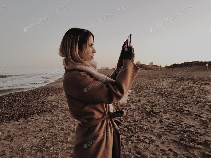 A beautiful woman takes a picture of the sunset in the beach.