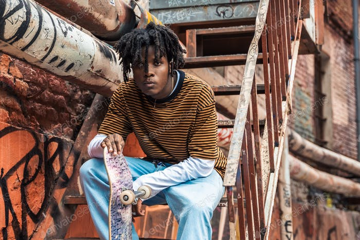 Portrait of young handsome stylish black man with natural hair dreadlocks. Afroamerican guy. Stairs,