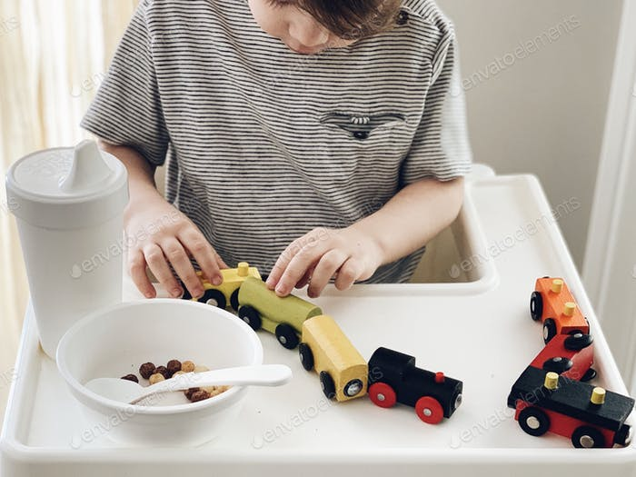 Toddler sitting in a high chair at mealtime playing with a wooden toy train