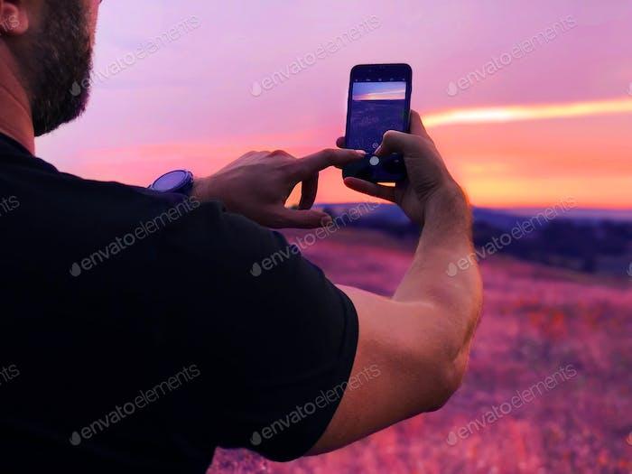 Joven tomando una foto de una puesta de sol púrpura sobre el campo en flor