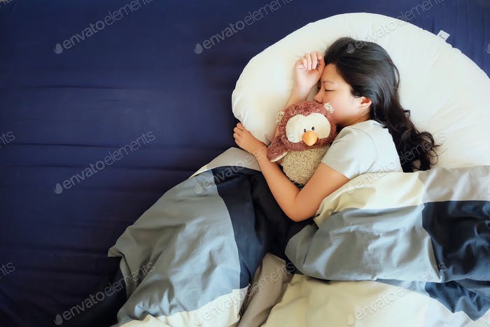 Asian girl sleeping comfortably while cuddling a stuffed owl