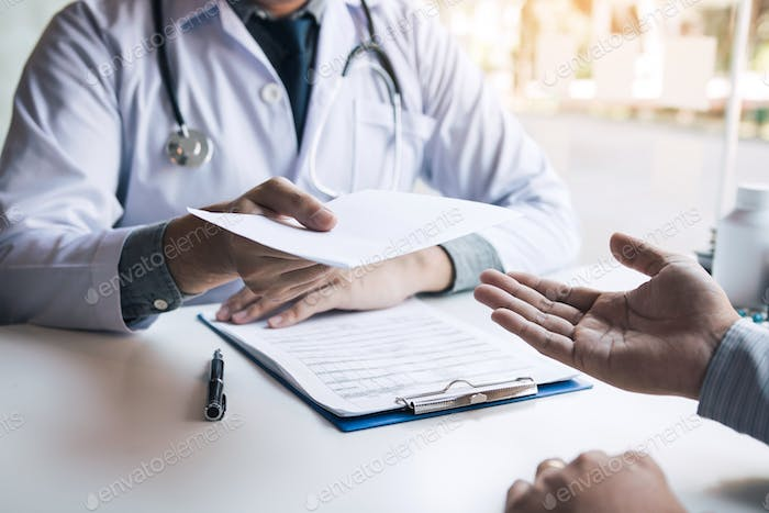 Asian male doctor talking in clinic room and handing a prescription to the patient.