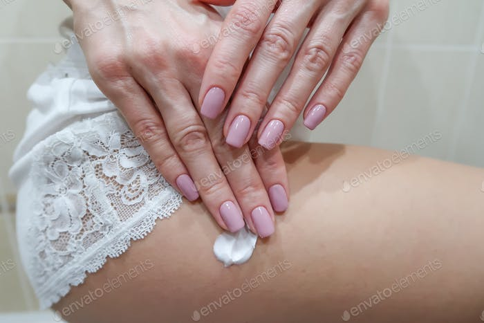 Woman is applying lotion on her body