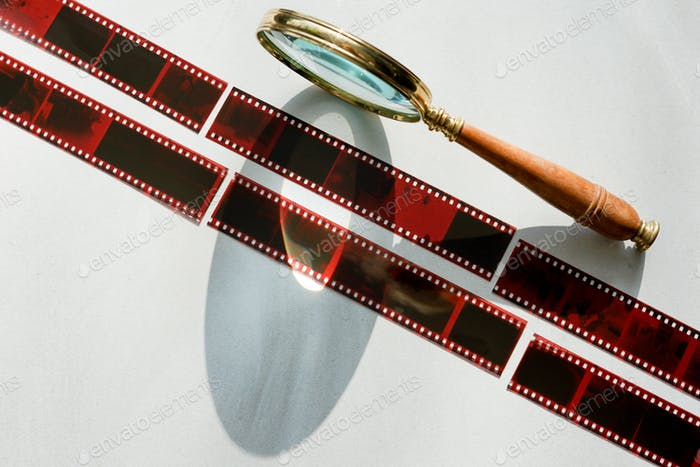 Analog photography filmstrip. Negatives and retro magnifying glass.