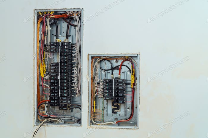 Electrical voltage switchboard box with wires with circuit breakers.