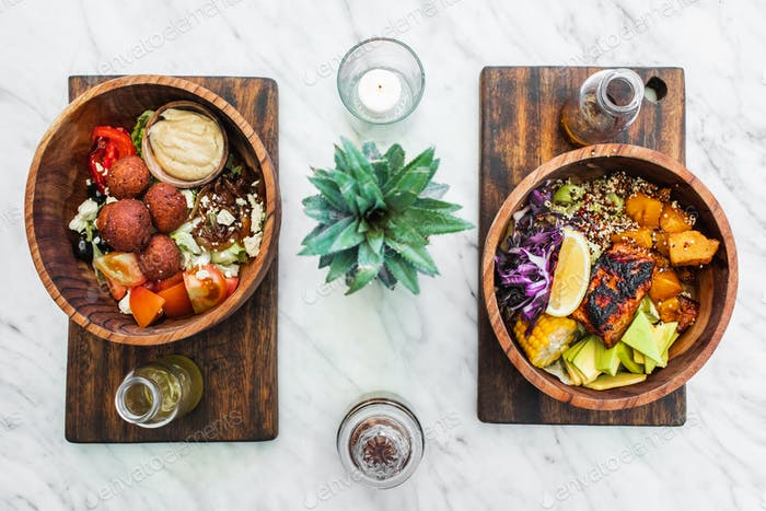 Flat lay of wooden bowls with fresh organic vegetarian food on white marble table. Falafel, hummus,