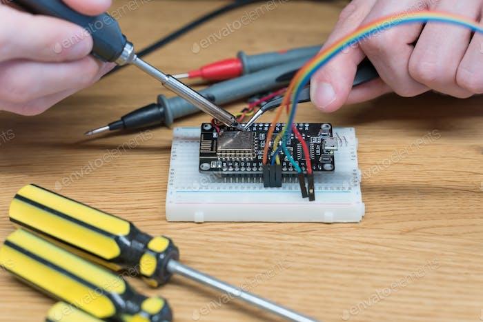 Technician engineer in workshop. Repairman is soldering circuit board of electronic device