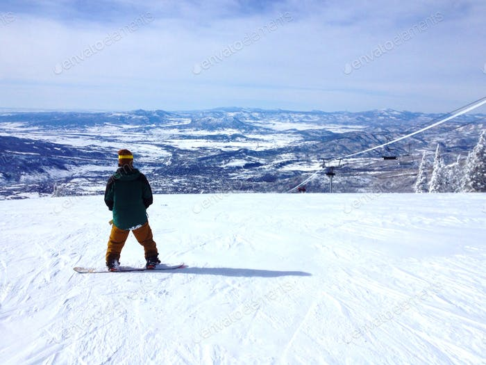 Snowboarder on top of a mountain enjoying the view.