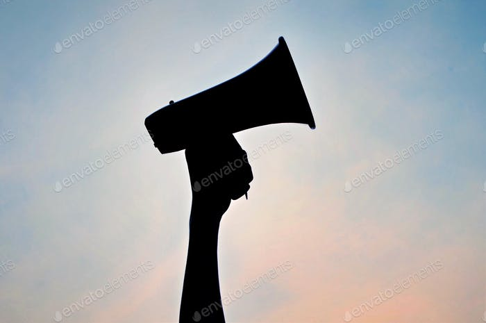 Silhouette of hand in the air holding megaphone against a pink and blue sky