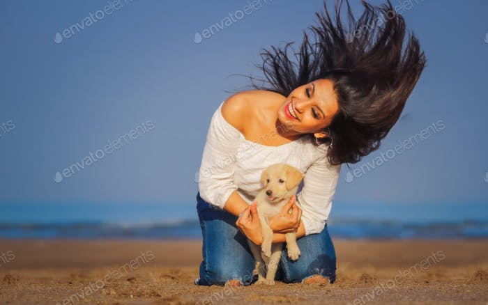 Beautiful lady having fun at the beach with her cute little pet