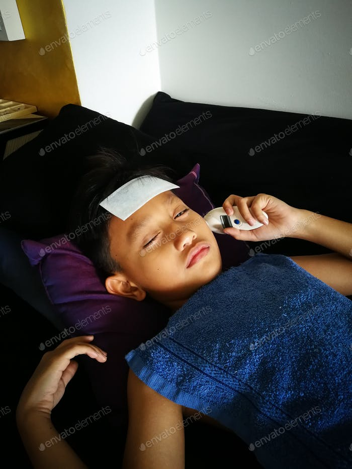 Junge überprüft seine eigene Körpertemperatur. Sich krank und unwohl fühlen
