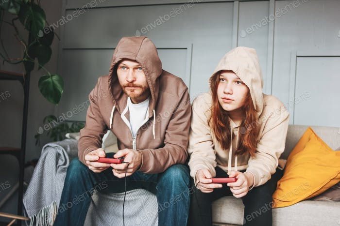 Father and teenager daughter tween girl in hoodies playing computer games with joystick at home tipi