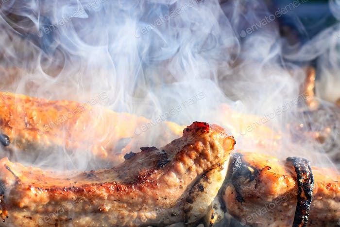 Barbecue skewers with juicy meat cooking in open air in summer. Food background.