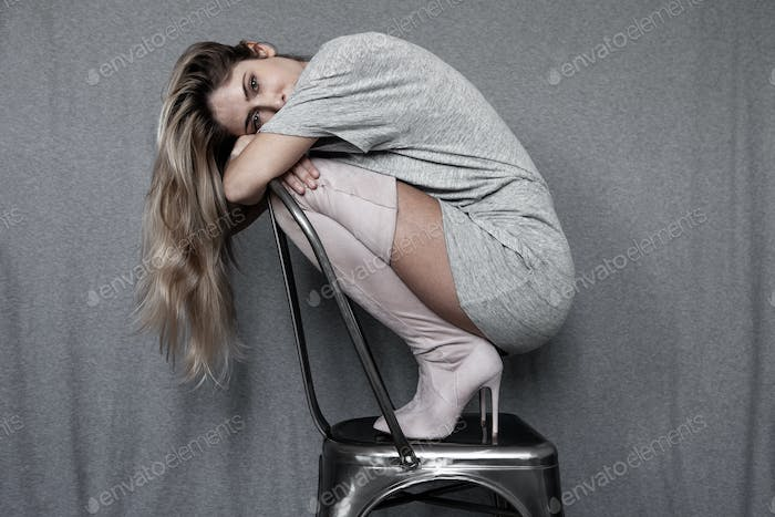 A beautiful woman shrinks on herself on a metal chair, wearing high-heeled boots.