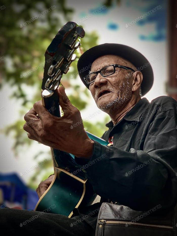 Ein alter Mann singt 70er Lieder beim Zupfen seiner Gitarre