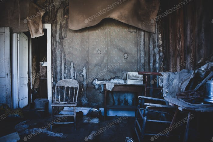 Abandoned house with old furniture and dilapidated walls and ceiling in a ghost town