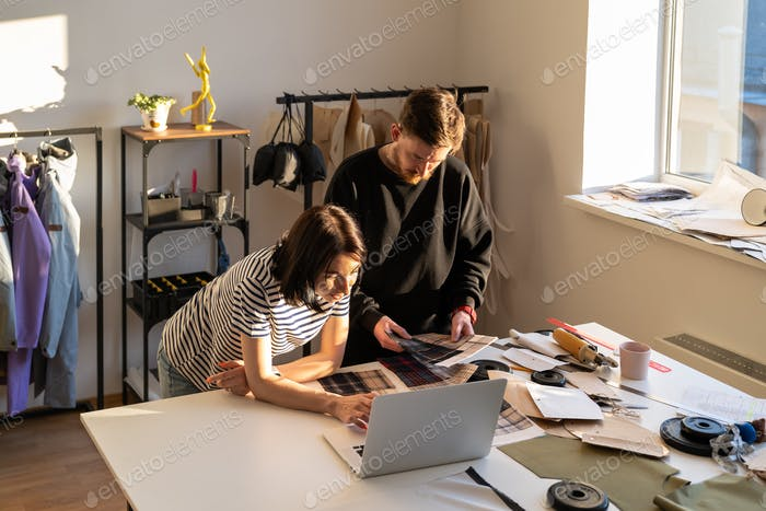 Team of designers work in studio. Tailors choose cloth for suit collection. Garment business concept