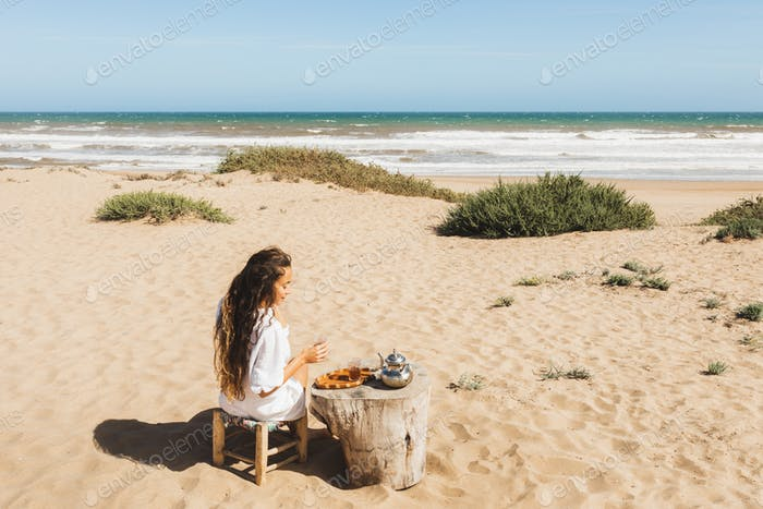 Young happy woman enjoying traditional moroccan mint tea outdoors on ocean sand beach in Morocco