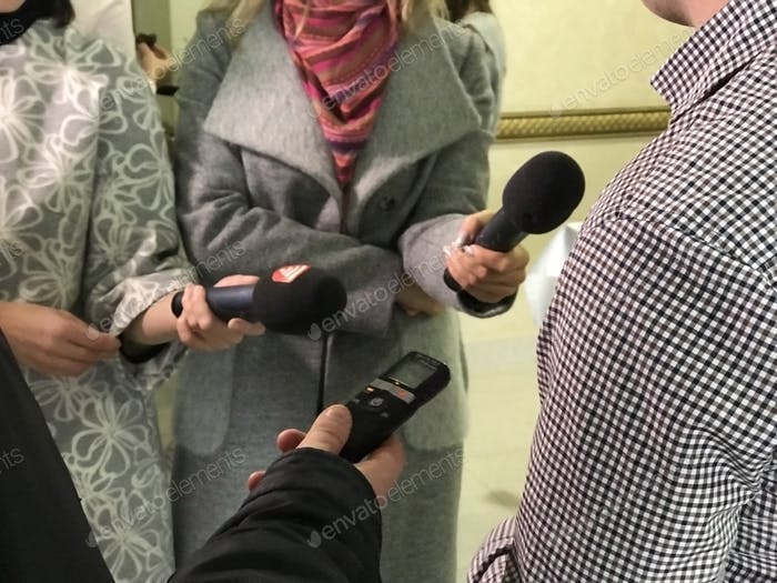 Journalists with microphones are interviewed