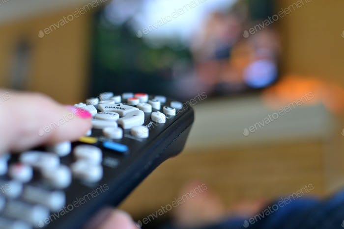 Woman holding a TV remote pointed at a big screen television while watching a movie or TV show.