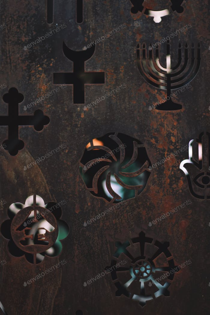 Religious and spiritual symbols cut out in a rustic metal
