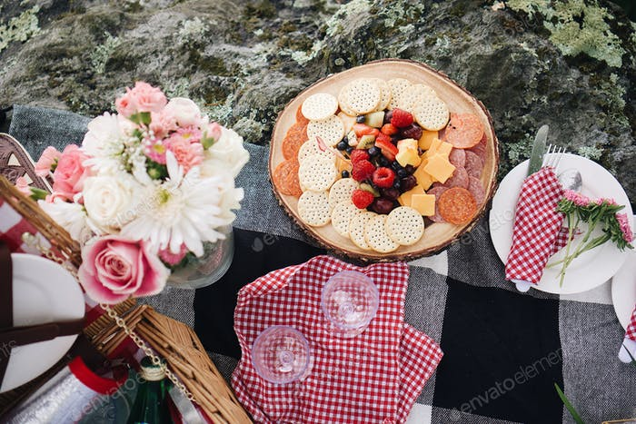 Picnic fruits and cheeses adorned by flowers